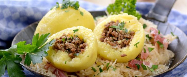 Gefuellte Kartoffelknoedel mit Speckkraut in der Pfanne serviert